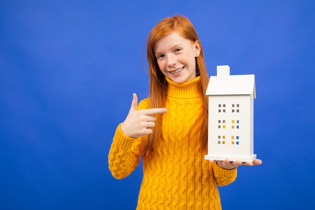 Girl holds a house model in hand on blue. the property