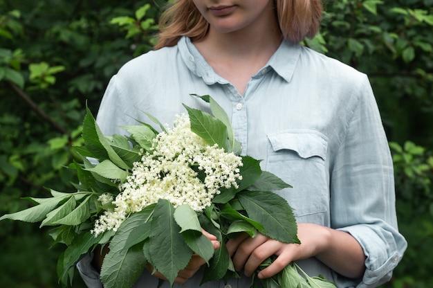 女の子は庭でニワトコの花を手に持っています