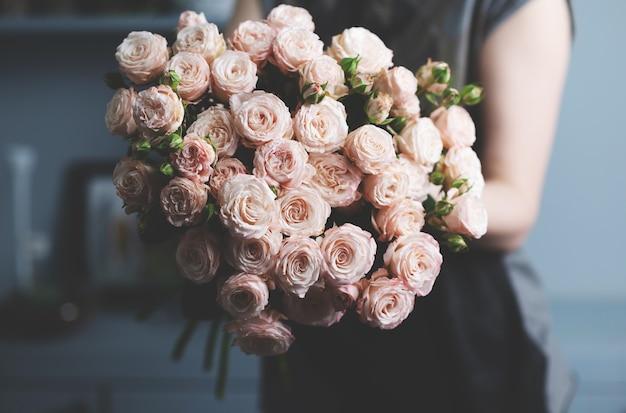 女の子は彼女の手でピンクのバラの美しい花束を持っています。