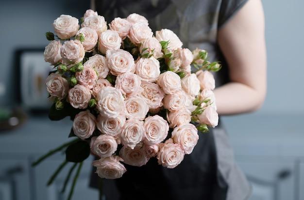 여자는 그녀의 손에 핑크 장미의 아름 다운 꽃다발을 보유하고있다.
