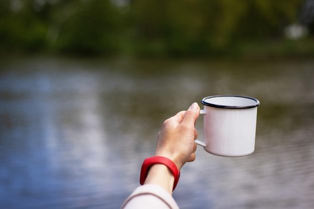 少女は彼女の手で湖の近くのコーヒーの金属のカップを保持しています。