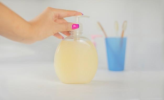 女の子は彼女の手で瓶の中の細菌に対する保護剤を保持します