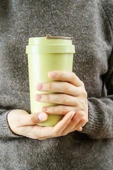소녀는 그녀의 손에 대나무 컵 제로 폐기물 개념 테이크 아웃 커피 나 보유