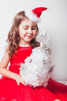 소녀는 손으로 만든 장식을 손에 들고 - 은색 리본으로 만든 크리스마스 트리