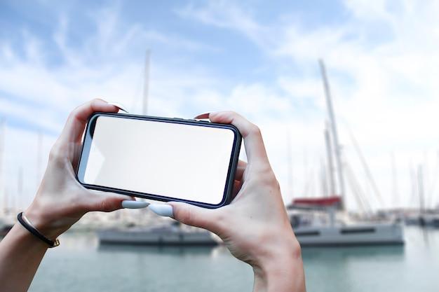 소녀는 바다와 요트를 배경으로 흰색 화면이있는 스마트 폰 클로즈업을 손에 들고 있습니다. 목업 기술.