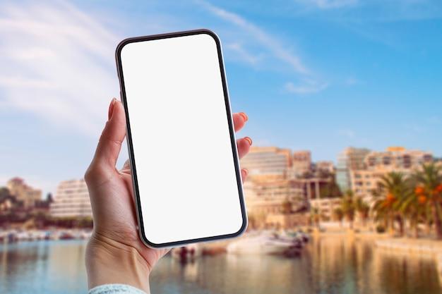 少女は、海とヨットを背景に白い画面でスマートフォンのクローズアップを手に持っています。モックアップテクノロジー。