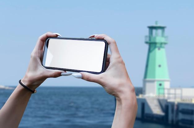 소녀는 바다의 배경에 흰색 화면으로 그의 손에 스마트 폰 클로즈업을 보유하고 있습니다. 목업 기술.