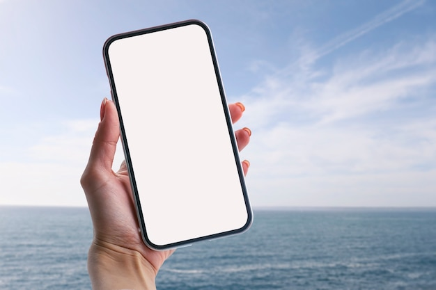 少女は、海を背景に白い画面でスマートフォンのクローズアップを手に持っています。モックアップテクノロジー。