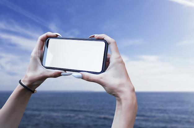 소녀는 바다의 배경에 흰색 화면으로 그의 손에 스마트 폰 클로즈업을 보유하고 있습니다.