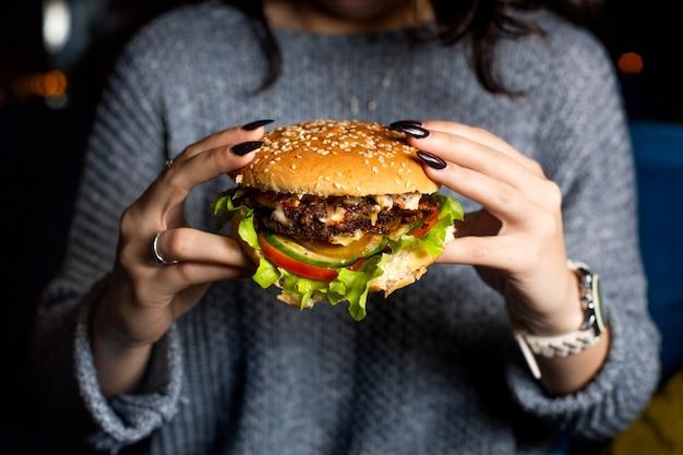 Девушка держит сочный чизбургер