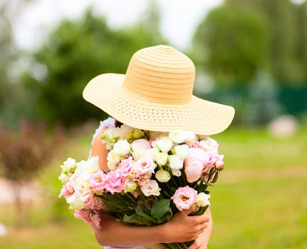 The girl holds a large bouquet of pink and white peonies in front of her.