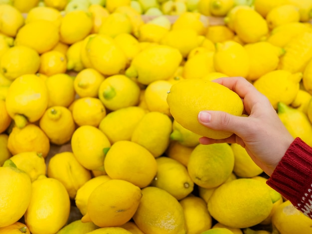 The girl holds a lemon in a hand.