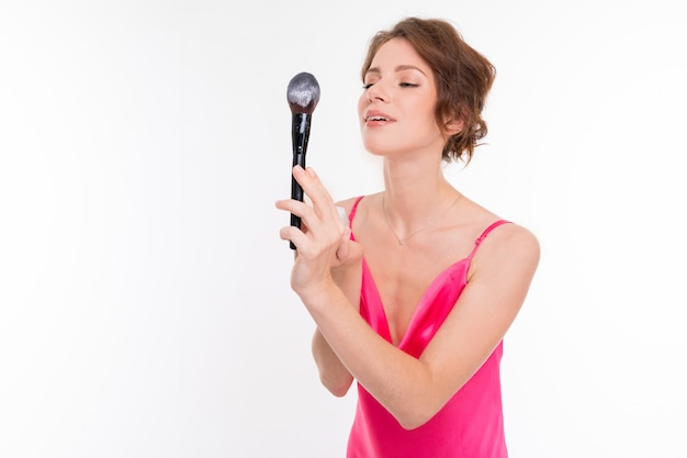 Girl holds a makeup brush with sparkles on a white wall