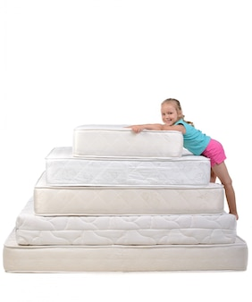 The girl holds the mattress and smiles.
