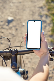 Girl holds a mobile phone riding on the bicycle. mockup