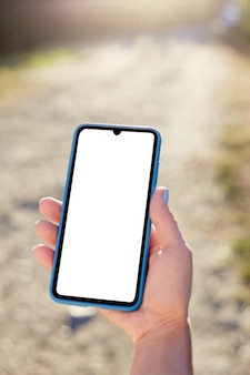 Girl holds a mobile phone on vacation in nature. mockup