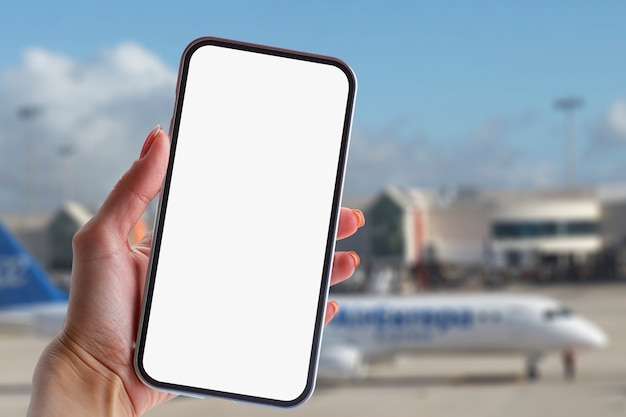 Girl holds a mock-up of a smartphone with a white screen close-up. phone on the background of the airport with an airplane.