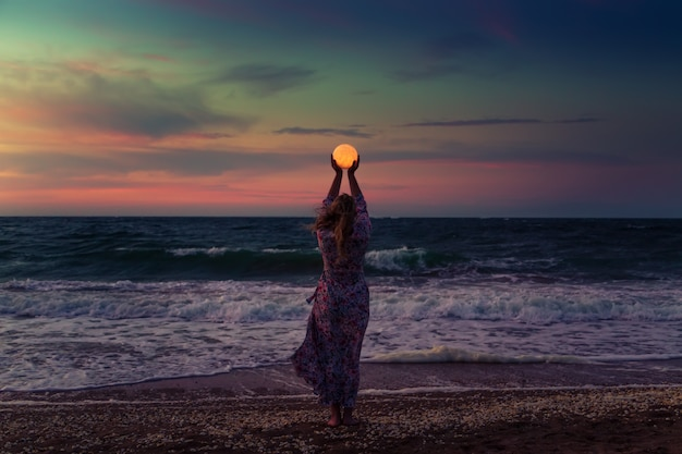 Girl holds the moon in her hands.