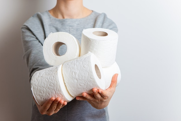 The girl holds out her hands full with toilet rolls.