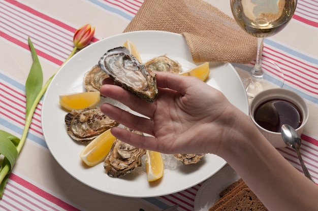 A girl holds an oyster against the background of a plate with oysters and lemon