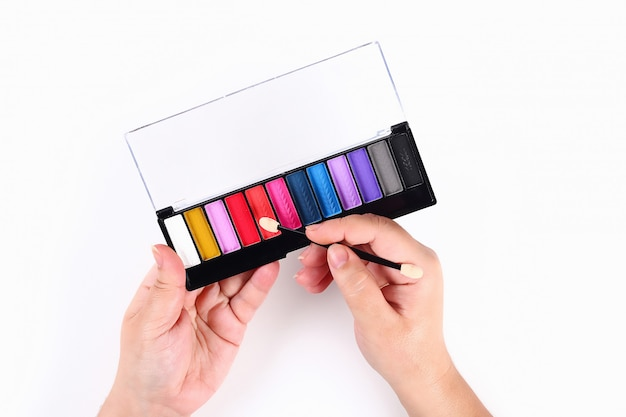 A girl holds a palette of eyeshadow in her hand on white. top view.