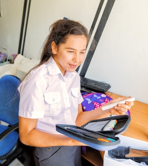 The girl holds a pencil case with markers and pencils in her hands