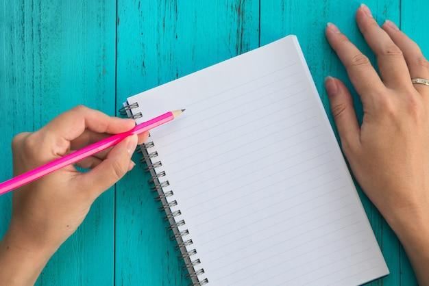 Девушка держит карандаш в левой руке, готовит записать цели на будущее в записной книжке, синий деревянный стол.