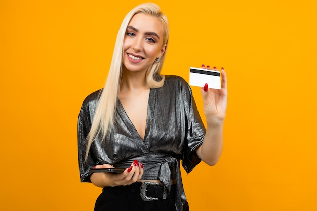 Girl holds a phone and a credit card with a mockup on an orange