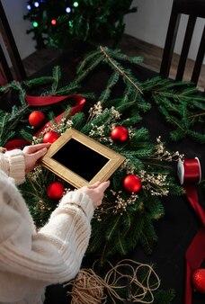 소녀는 집에서 테이블에 장식 된 크리스마스 화 환 위에 사진 프레임을 보유