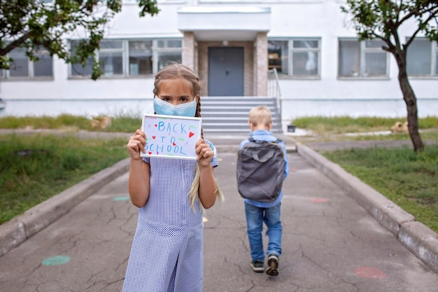 Girl holds picture with back to school message and boy goes to school after first offline day
