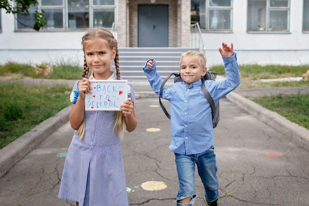 Девушка держит фотографию с посланием обратно в школу, а мальчик с рюкзаком бежит после первого дня офлайн