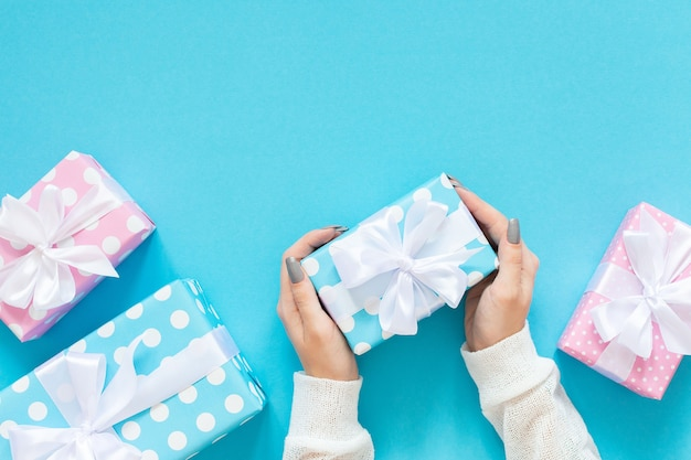 Girl holds pink and blue gift boxes in polka dots with white ribbon and bow