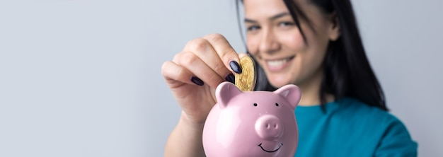 The girl holds a pink piggy bank and a coin in her hands. the concept of wealth and accumulation.