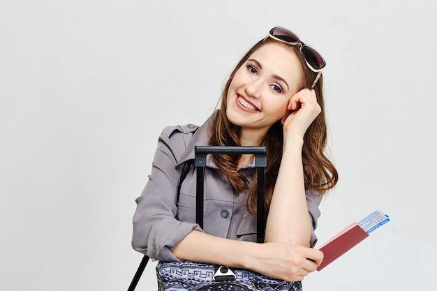 Девушка держит билеты на самолет с багажом как концепция перемещения.