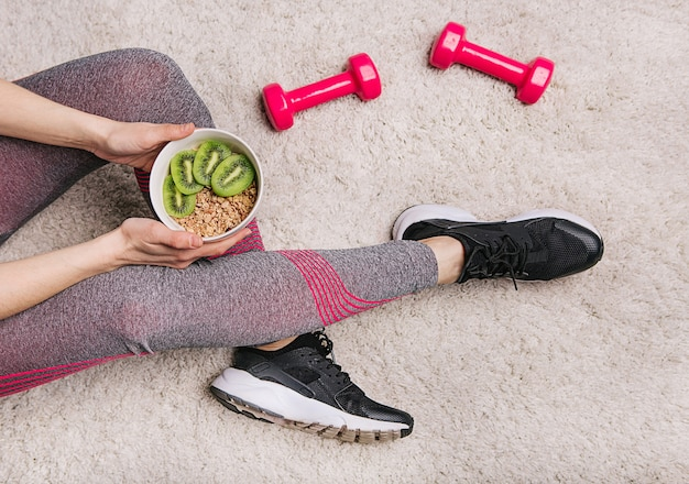 Girl holds a plate with muesli and kiwi after fitness workout with dumbbells