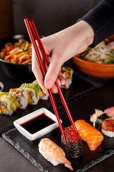 A girl holds a red chinese chopsticks and eat sushi in a restaurant.