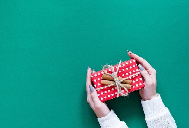 소녀는 녹색 배경, 메리 크리스마스와 새해 복 많이 받으세요 개념, 평면 평신도, 평면도에 계피와 물방울 무늬에 빨간색 선물 상자를 보유하고 있습니다.