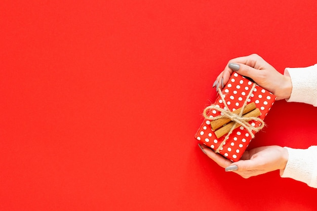 Girl holds red gift box in polka dots with cinnamon on a red background, merry christmas and happy new year concept, flat lay, top view