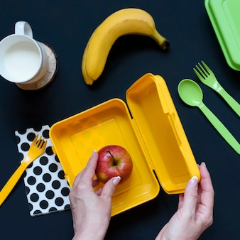 Girl holds school lunch box, mug of milk, apple and bananas on a dark background. top view. flat lay. healthy eating habits concept. home food for office concept.