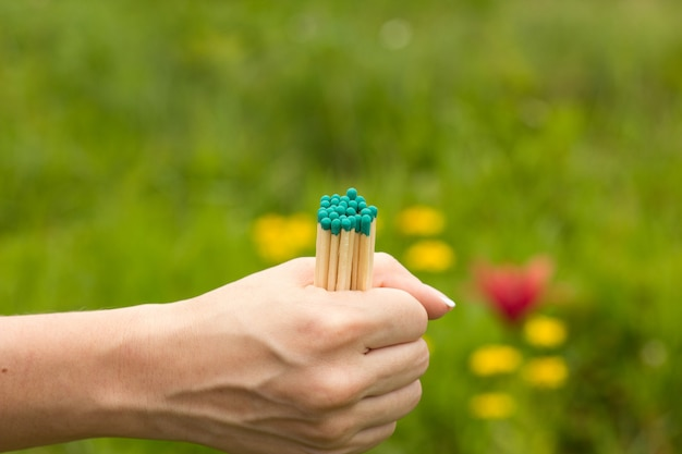 The girl holds several matches in her hand on a blurred background