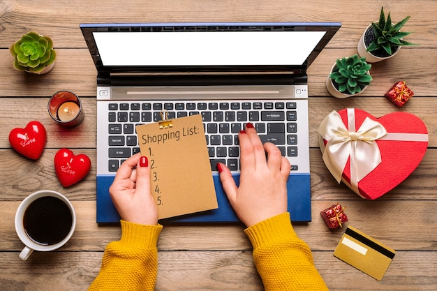 Girl holds shopping list, debit card, chooses gifts, makes purchase, laptop, coffee cup
