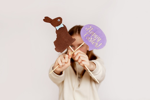 Girl holds a sign saying happy easter and brown felt rabbit