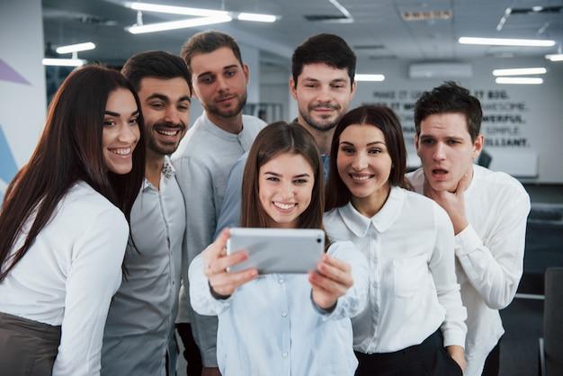 女の子は銀色の電話を保持しています。現代の良い明るいオフィスでクラシックな服でselfieを作る若いチーム