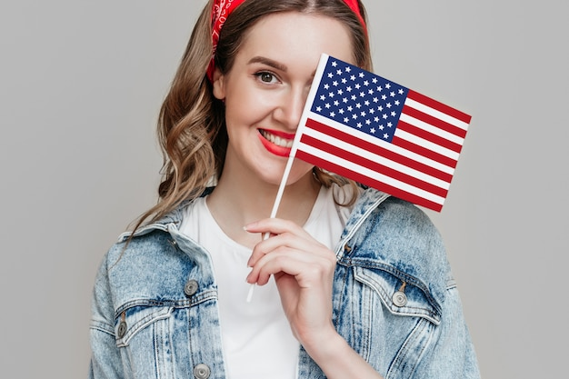 Girl holds a small american flag and smiles isolated over orange background 4th of july independence day