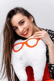Девушка держит в руках мягкую игрушку. мягкая игрушка в виде зуба в очках. концепция ухода за полостью рта.