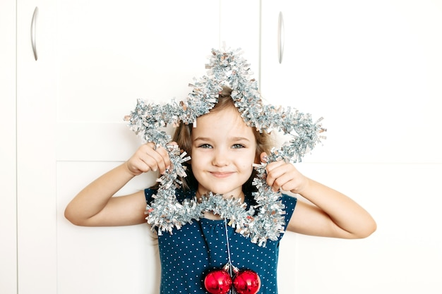 A girl holds a star in her hands to decorate the house for the new year and christmas, the child is preparing for the holiday, helping parents, waiting for gifts