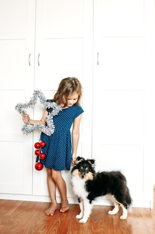 A girl holds a star in her hands to decorate the house for the new year and christmas, a dog puppy shelty child preparing for the holiday, helping parents, waiting for gifts