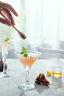 Girl holds a stick over exotic cocktail