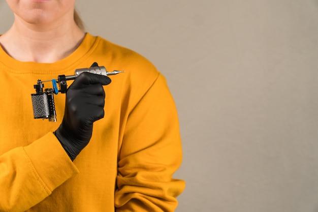 Girl holds a stylish tattoo machine black permanent