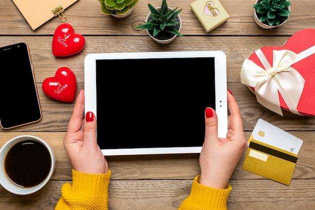 Девушка держит планшет, дебетовую карту, выбирает подарки, делает покупки, кофейную чашку, два сердца, сумку на деревянном столе